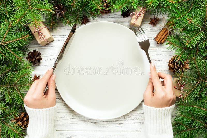 Top view girl holds fork and knife in hand and is ready to eat. Empty plate round ceramic on wooden christmas background. holiday. Dinner dish concept with new stock images