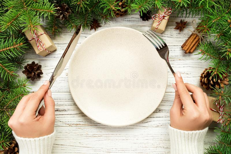 Top view girl holds fork and knife in hand and is ready to eat. Empty plate round ceramic on wooden christmas background. holiday. Dinner dish concept with new royalty free stock image