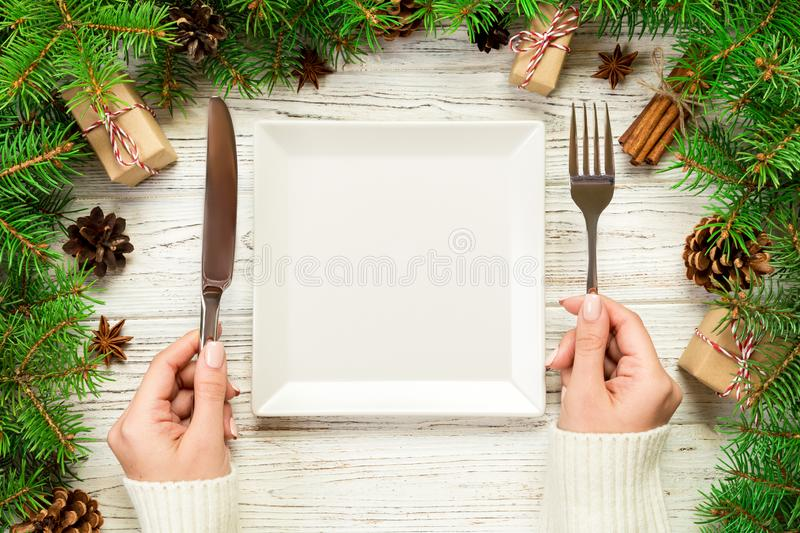 Top view girl holds fork and knife in hand and is ready to eat. Empty white square plate on wooden christmas background. holiday. Dinner dish concept with new royalty free stock photo