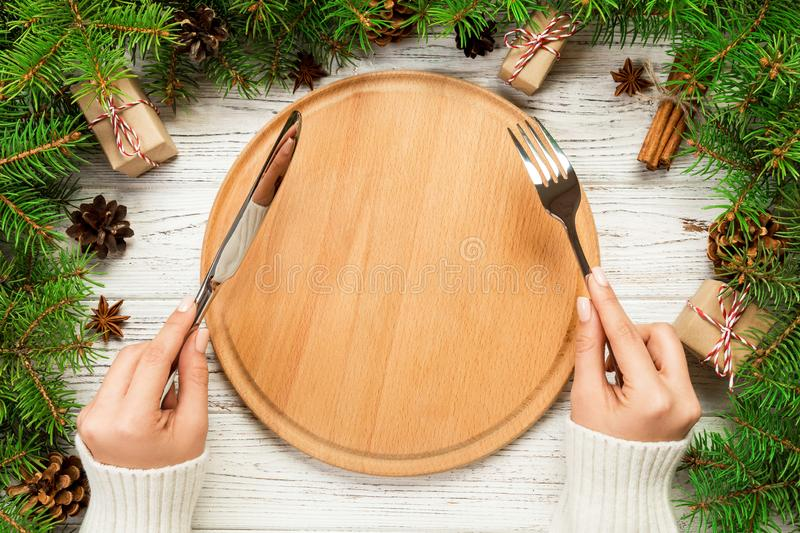 Top view girl holds fork and knife in hand and is ready to eat. Empty wood round plate on wooden christmas background. holiday. Dinner dish concept with new stock images