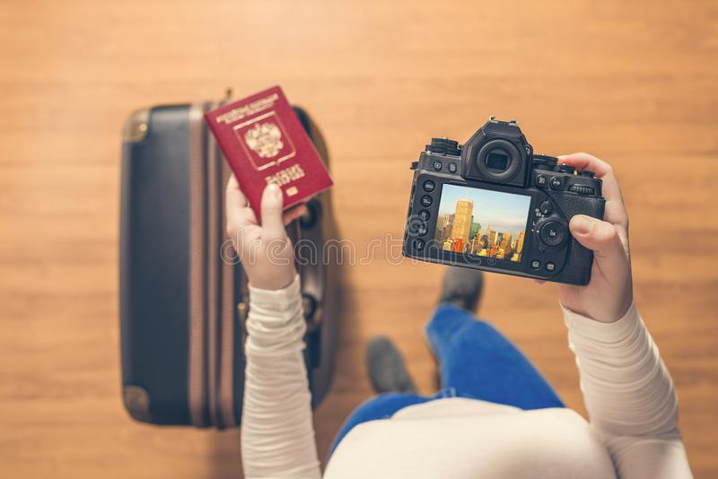 Top view on a girl looking a photos from New York city on her camera standing with suitcase in the airport. royalty free stock photo