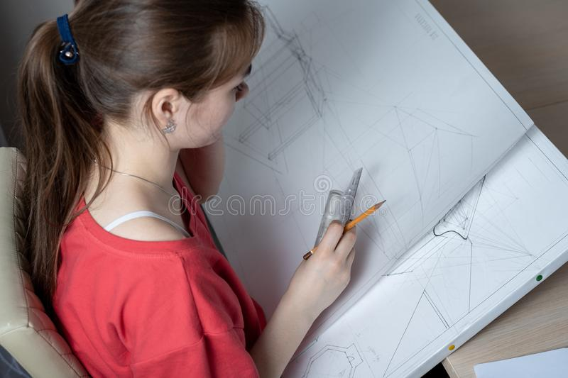 Top view of the girl student of architectural University, draws a work plan.  royalty free stock photo