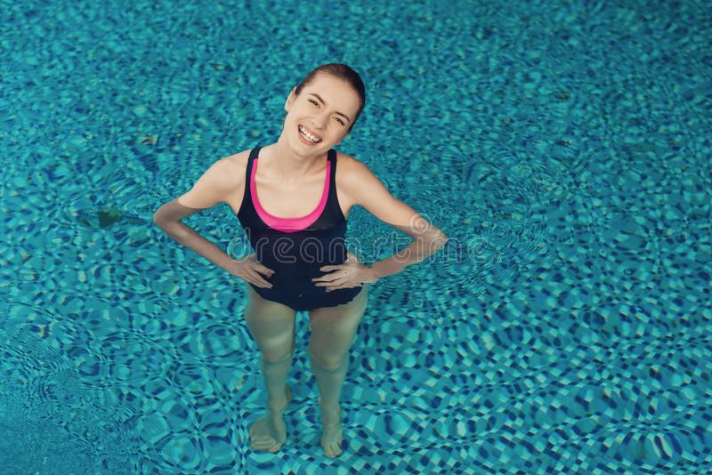 Top view girl inside the pool at the gym. She looks happy, fashionable and fit in one piece. stock images