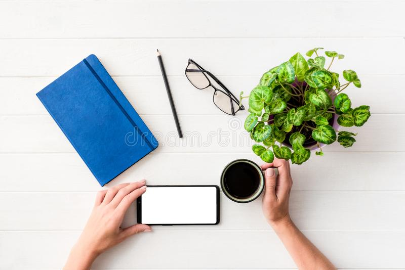 Top view of girl using smartphone at working place. Composition background royalty free stock image