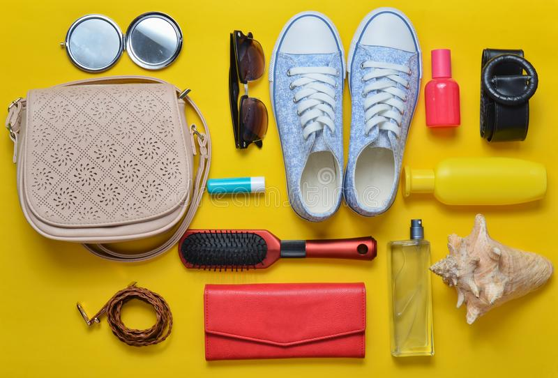 Top view of the girlish spring-summer accessories: sneakers, cosmetics, beauty and hygiene products, bag, sunglasses on a yellow p. Astel background. Going on a stock images