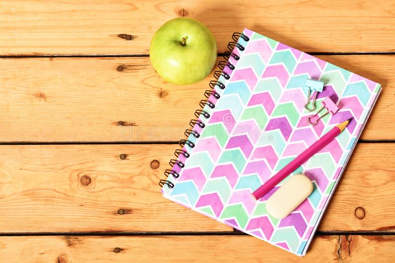 Pink notebook and apple on wooden background. Top view of girly pink notebook with pencil, eraser, binder clips and apple on wooden background stock photos