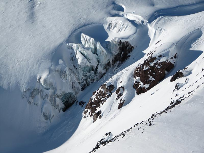 Top view of the glacier and snow-capped mountains and protruding rocky cliffs on a Sunny day stock photo