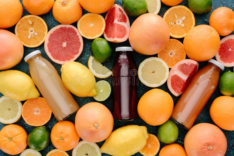 Top view of glass bottle of fresh juice surrounded with citrus fruits slices on blue. Concrete surface stock photo