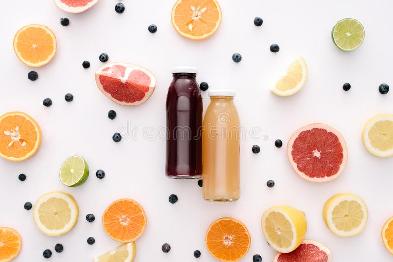 Top view of glass bottles of fresh juice with citrus fruits slices. On white surface stock photo