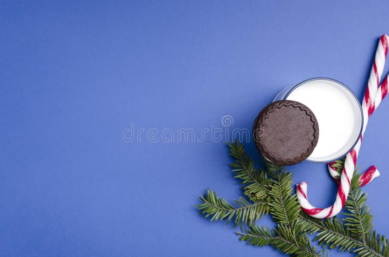 Top view of glass of milk and chocolate cookies for Santa Claus, candy canes. Traditional Christmas snack on the blue background.E stock photos