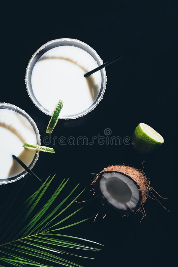 Top view of glasses with coconut cocktails and drinking straws, lime and green palm leaves. On black royalty free stock photo