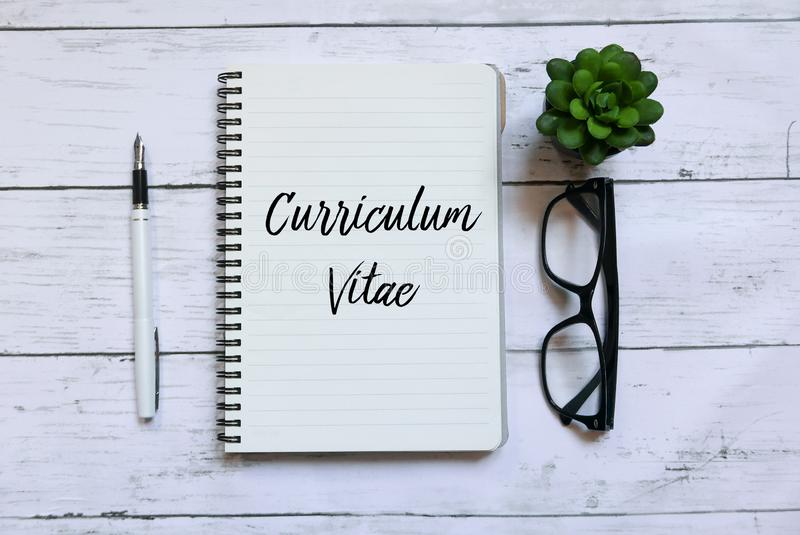 Top view of glasses,pen and notebook written with Curriculum Vitae on white wooden background. royalty free stock photos