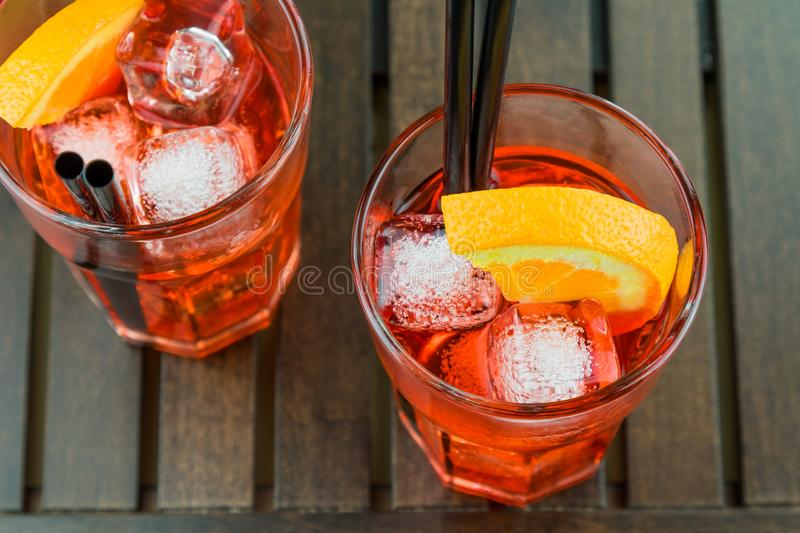 Top of view of glasses of spritz aperitif aperol red cocktail with orange slices and ice cubes. On wood table stock images