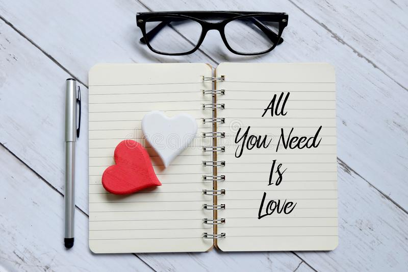 Top view of glasses,wooden heart,pen and notebook written with All You Need Is Love.Advice and motivation. Top view of glasses,wooden heart,pen and notebook stock images