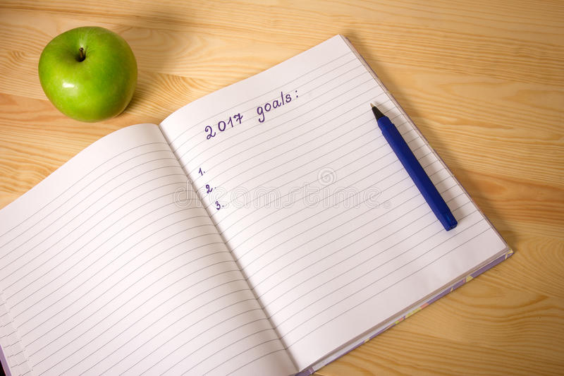 Top view 2017 goals list with notebook, green apple on wooden desktop. Success concept stock photography