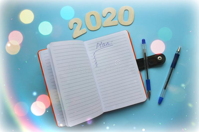 Top view of 2020 goals list with Notepad on blue background. royalty free stock photography