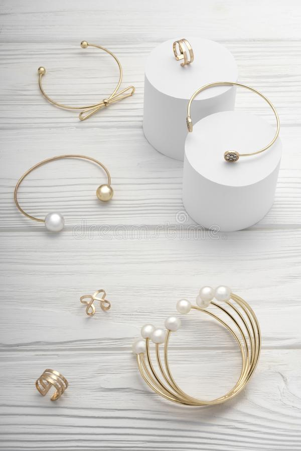 Top view of golden girl accessories bracelets and rings collection on wooden background stock image