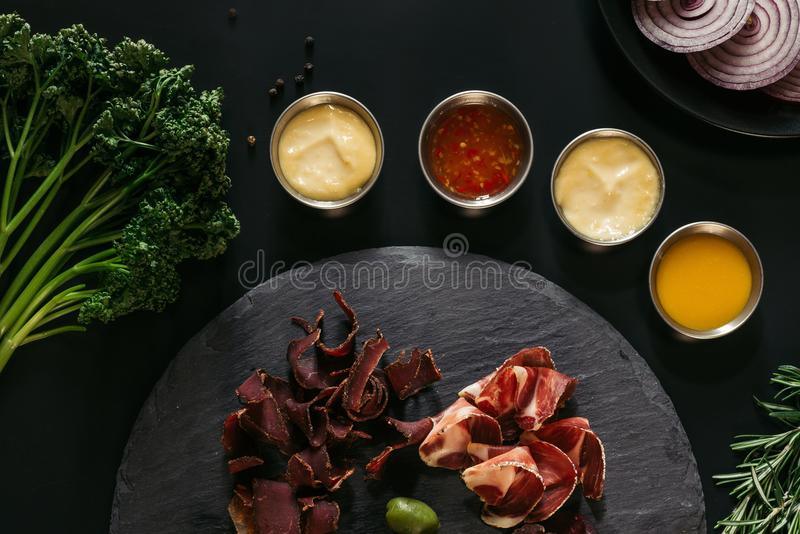 top view of gourmet craft meat with various sauces on black stock photography