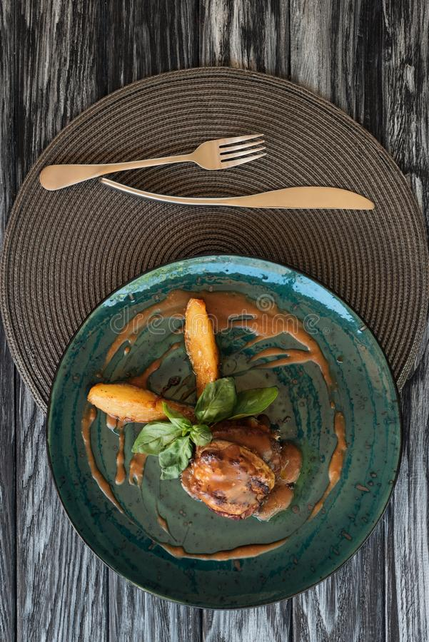top view of gourmet ribeye beef steak with basil, fork and knife stock image