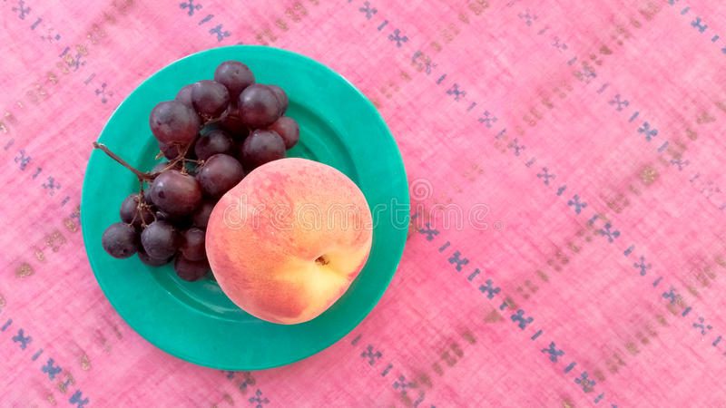 Top View of Grapes With Peach in a Plate. Top View of Grapes With Peach Served in a Plate royalty free stock images