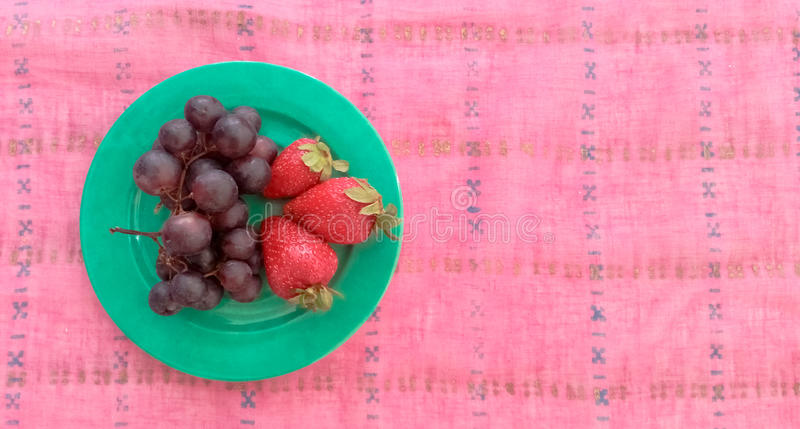 Top View of Grapes With Strawberries in a Plate. Top View of Grapes With Strawberries Served in a Plate royalty free stock photography