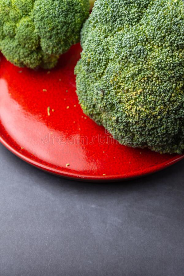 Top view of green broccoli on red plate and dark surface in vertical, with selective focus royalty free stock image