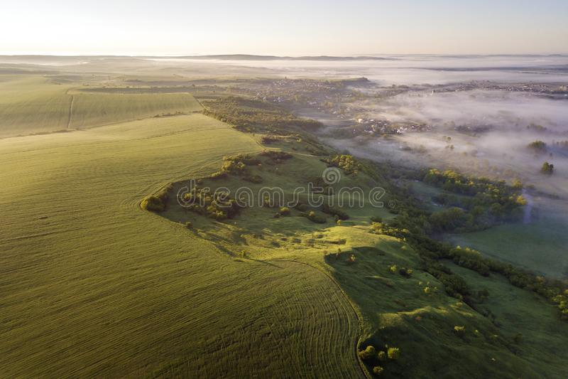 Top view of green cultivated hills, green trees and small houses in foggy valley on bright blue sky copy space background. Spring. Top view of green cultivated stock photo