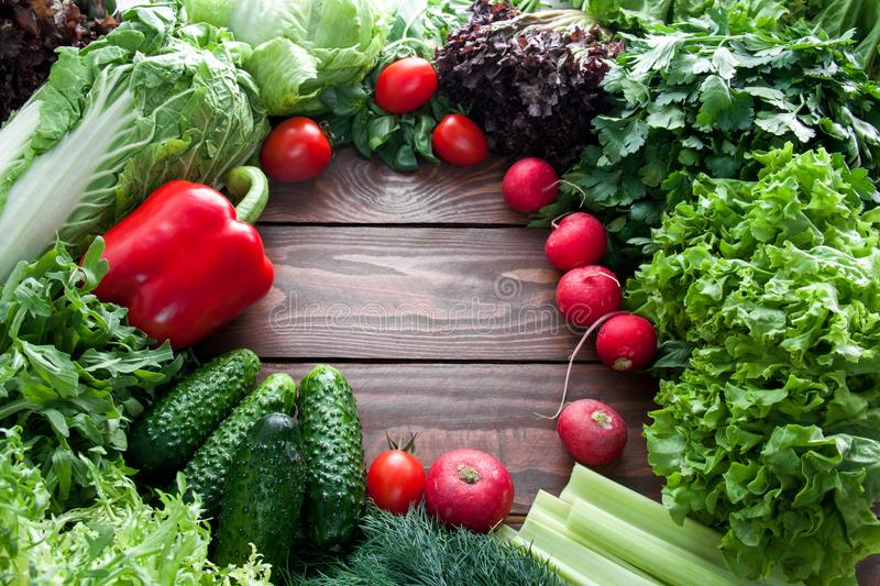 Top view of green lettuce leaves, cucumber and red vegetables on wooden table with place for text centered stock photo
