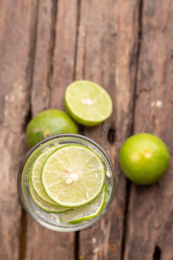 Top view green lime sliced in the soda water and glass place on the wooden table royalty free stock photos