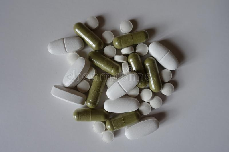 Top view of green moringa capsules, white calcium caplets and vitamin K tablets. Top view of green moringa capsules, white calcium caplets and vitamin K2 tablets royalty free stock photos