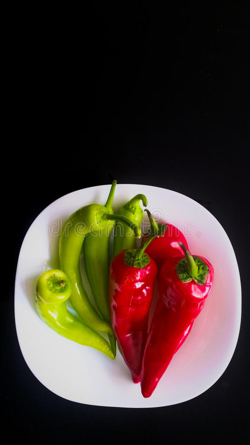Top view of green and red peppers in a white plate on a black background. Top view of green and red peppers in a white plate stock images