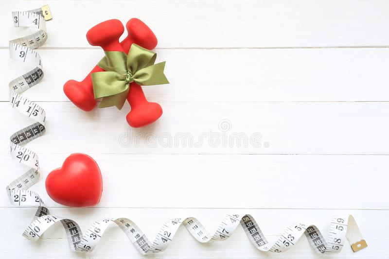 Top view of Green ribbon with dumbells and measuring tape of healthy heart on wooden white background, Health care concept royalty free stock photo