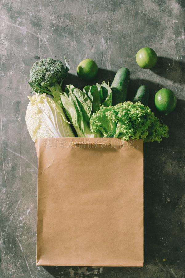 Top view of green vegetables in shopping bag on wooden table royalty free stock photo