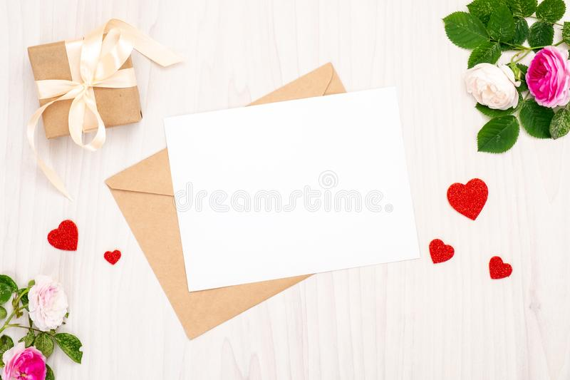 Top view greeting card with a red heart shapes and space for text, gift box with ribbon bow and rose flowers on a wooden royalty free stock images