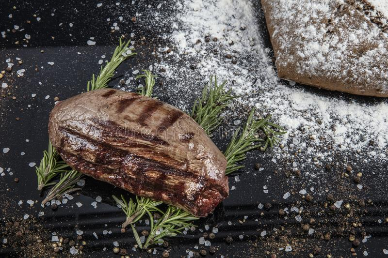 Top view of grilled filet mignon beef steaks on a black wooden surface royalty free stock images