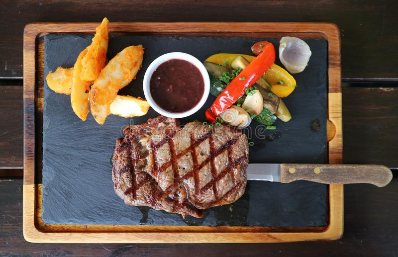 Top view of grilled ribeye steak with red wine sauce served on hot stone plate royalty free stock images