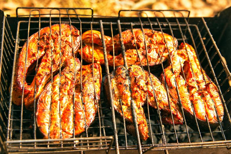Top view grilled salmon on flaming braai. Grilling salmon steak with ginger marinade in wire rack over barbecue. Top view grilled salmon on flaming braai stock photo