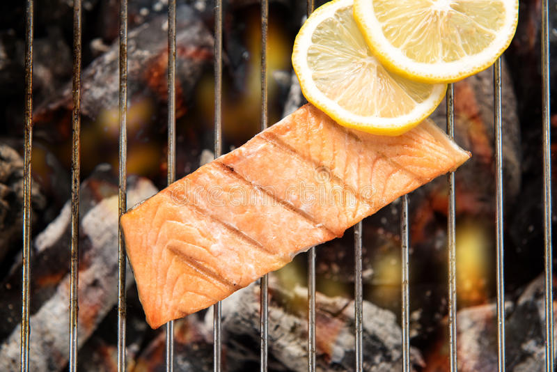 Top view grilled salmon with lemon on the flaming grill. stock photos