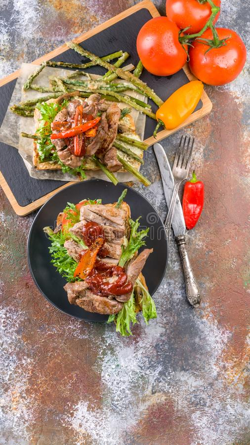 Top view Grilled turkey meat with sweet peppers, tomatoes and herbs on a cutting board. Mediterranean Kitchen. Vertical shot stock photos