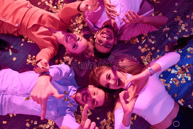 Clubbers on Party Floor. Top view at group of happy young people gesturing hearts and thumbs up lying on floor among confetti and looking at camera during royalty free stock images