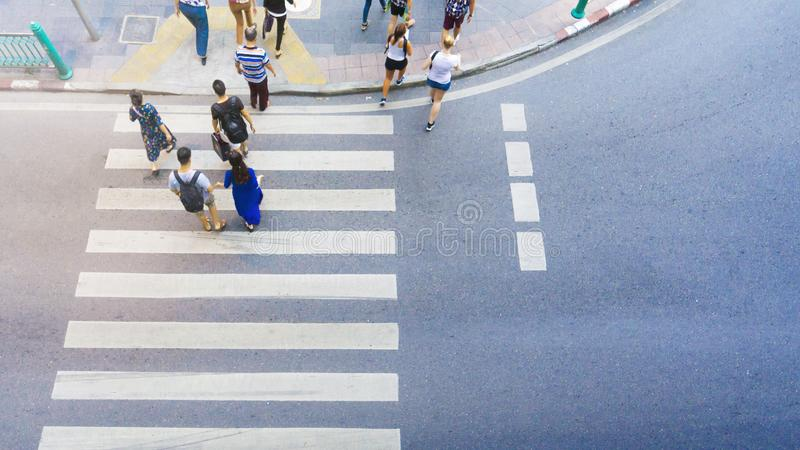 Top view of group men and women and people walk on the crosswalk. With white sign pedestrian on the city street aerial city street view stock images