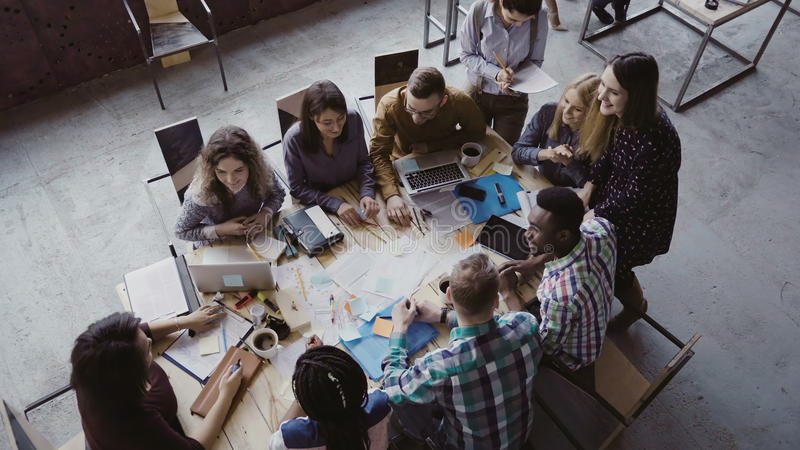 Top view of group of mixed race people sitting at table, talking and then start to clapping together. Business meeting. Top view of group of young mixed race stock photos
