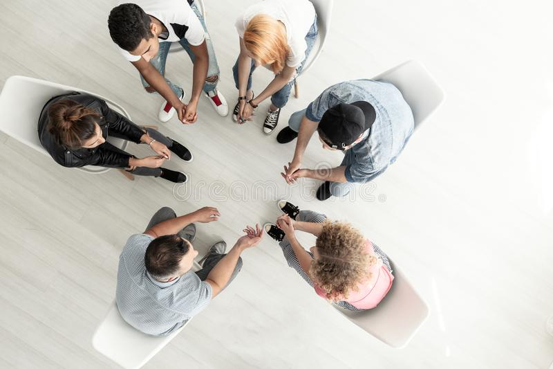 Top view on group of teenagers sitting in a circle during consul. Tation with counselor stock image