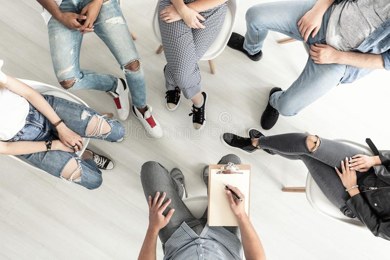Top view of a group therapy session for teenagers struggling wit stock image
