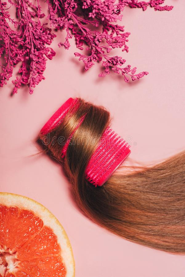 Top view of hair rolled over curler with flowers and orange. On pink surface royalty free stock image