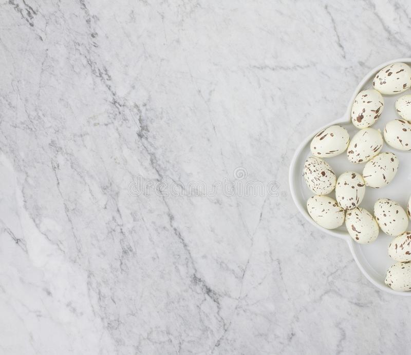 Top view of a half white plate with imitated specks quail eggs on the marble background stock photo