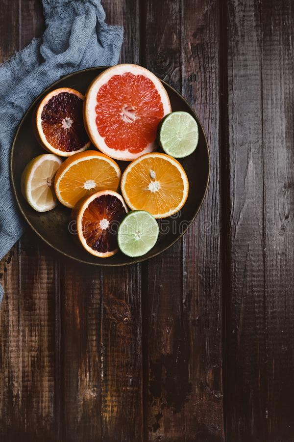 top view of halfs of orange, grapefruit, lime, blood orange and lemon in plate and kitchen towel royalty free stock images