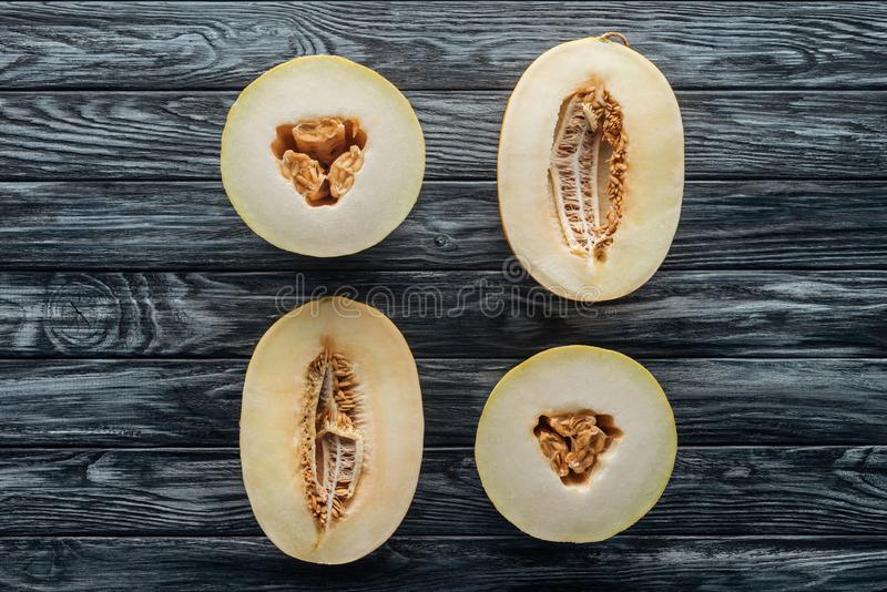 Top view of halved ripe sweet honeydew and cantaloupe melons on wooden. Surface royalty free stock photos