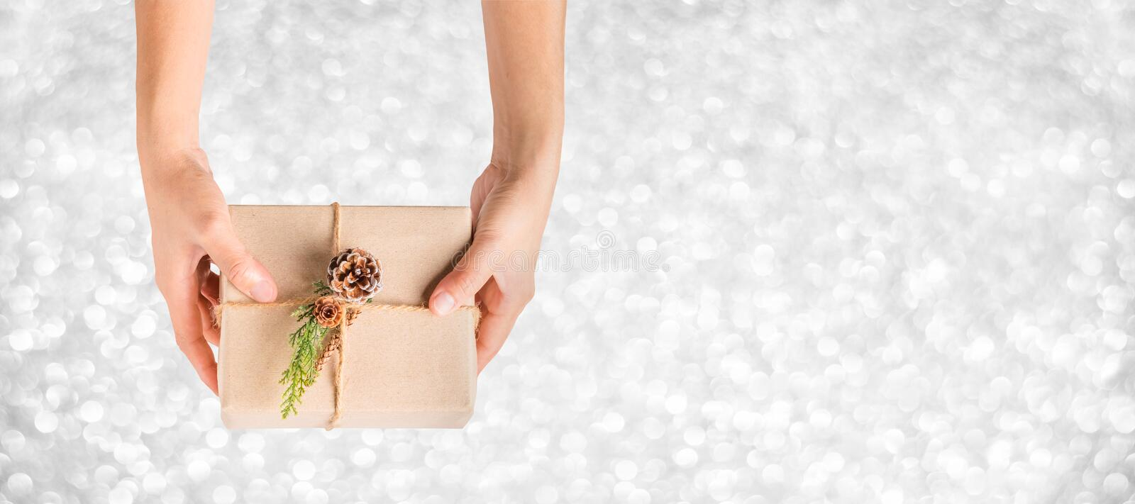 Top view hand holding xmas present box with silver sparkle bokeh background,Banner mock up for adding your text,chrismas Gift stock photos