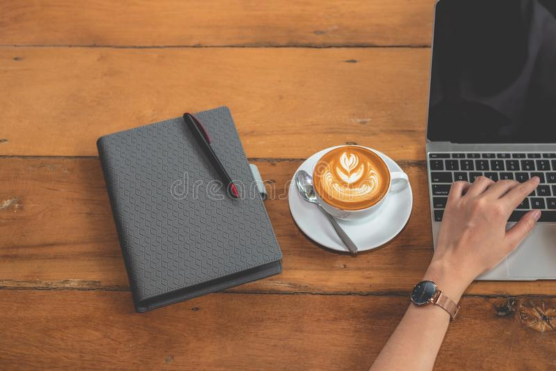 Top view of hand of woman using laptop computer with notebook and coffee cup. People and drinks and technology concept. Working royalty free stock photo